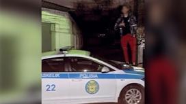 Молодой человек стоит на служебной машине полицейского