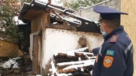 Сотрудник МЧС стоит возле горевшей бани