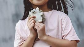 Девочка держит игрушку в руке