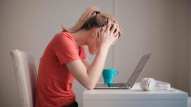 Женщина сидит за компьютером и держится за голову