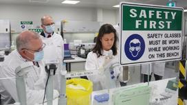 Ученые в лаборатории в белых халатах и масках