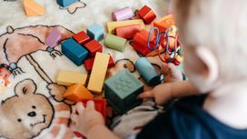 Младенец играет разноцветными кубиками, сидя на покрывале с медведем