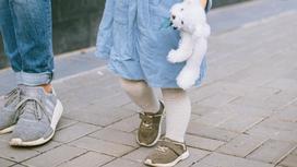 Мужчина идет по улице с дочерью