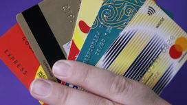Женщина держит веер из банковских карт