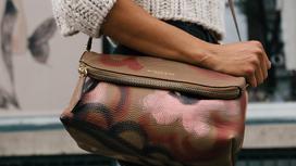 Девушка держит сумку рукой
