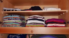 Аккуратно сложенные в шкаф футболки