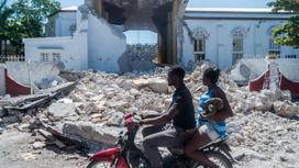 Жители Гаити проезжают около разрушенных зданий
