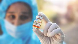 Врач из Индии держит вакцину