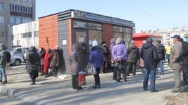 Люди стоят в очереди к киоску