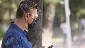 Мужчина в синей рубашке и черной маске смотрит на телефон