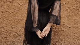 Девушка в черном платье стоит у стены