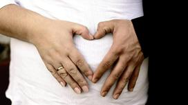 беременная держится за живот вместе с мужем
