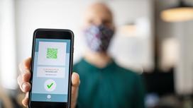 Мужчина в маске держит смартфон с QR-кодом на дисплее