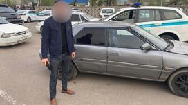Мужчина с замазанным лицом стоит возле поврежденной ножом машины