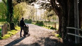 Мужчина гуляет с ребенком в коляске