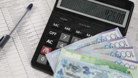 Бумажные деньги лежат на калькуляторе