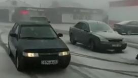 Машины едут во время снега