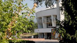 Здание алматинского цирка за ветками деревьев