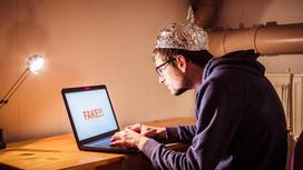 Парень в шапке из фольги за ноутбуком с надписью Фейк