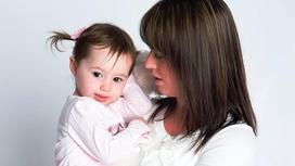 Мама держит дочку на руках