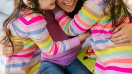 Женщина обнимает двух дочерей