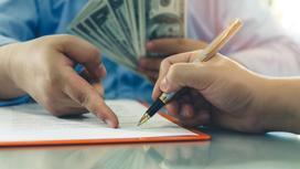 Мужчина подписывает кредитный договор