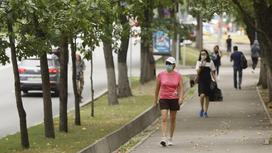 Девушка в спортивной одежде и маске идет по улице