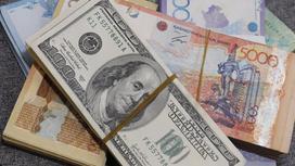 Пачка долларов лежит среди пачек тенге