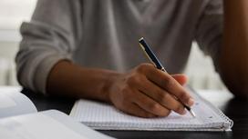 Студент пишет ручкой в блокноте