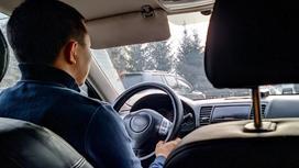 Водитель машины держится за руль