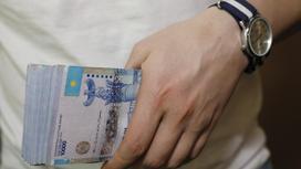 Пачка банкнот в руке у человека