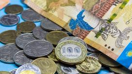 Монеты тенге лежат под купюрами тенге