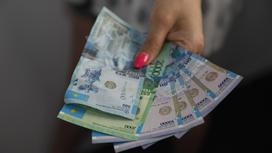 Женщина держит минимальную зарплату в РК