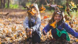 Девочки играют с осенними листьями