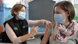 Женщина получает прививку в плечо