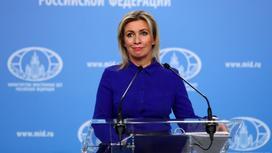 Женщина в синей рубашке за трибуной