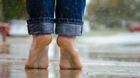 Человек в джинсах стоит под дождем