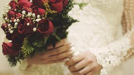 Невеста держит в руках букет красных  роз