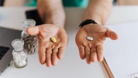 Две мужские руки с таблетками разного цвета