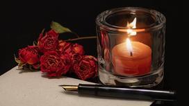На столе ручка, лист и горящая свеча