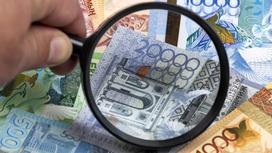 Мужчина смотрит через лупу на деньги