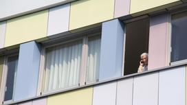 Мужчина стоит у открытого окна