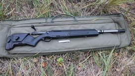 Черное ружье лежит на сумке на земле