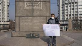 Мужчина стоит с плакатом возле монумента