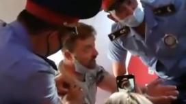 Авиапассажир сидит в окружении полицейских