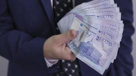 Мужчина в костюме держит в руках крупную сумму денег