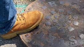 Человек наступил ногой на канализационный люк