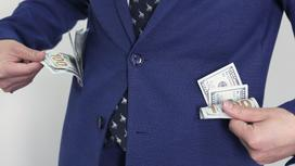 у мужчины из карманов пиджака торчат доллары