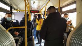 Пассажиры стоят в салоне автобуса