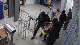 Задержанного ведут сотрудники СОБР